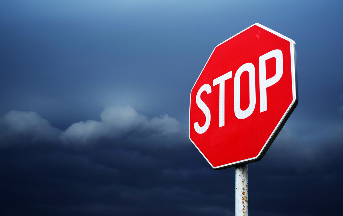 Stop sign on stormy background