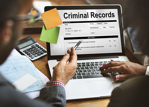 Employees Looking at Criminal Records on Computer Screen
