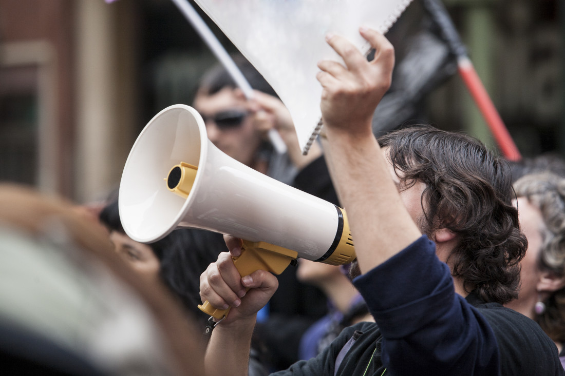 Demonstrator with Megaphone and Notebook Protesting
