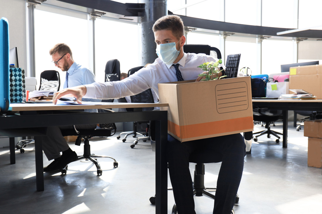 Employee being terminated during pandemic packing up belongings at desk