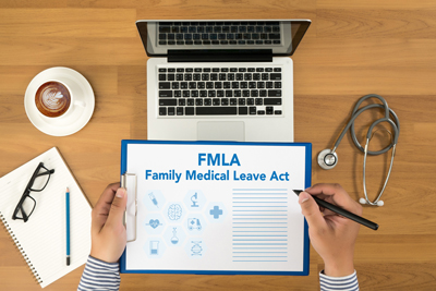 "Laptop with paper heading ""FMLA"" in foreground"