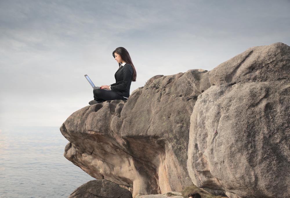 Woman typing on laptop on mountain