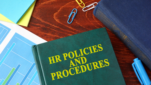 Book with title HR policies and procedures on a table